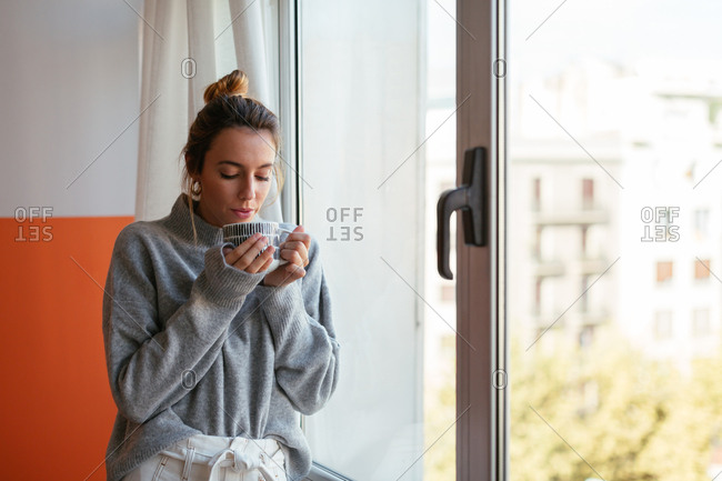 Woman drinking coffee next to a window at home