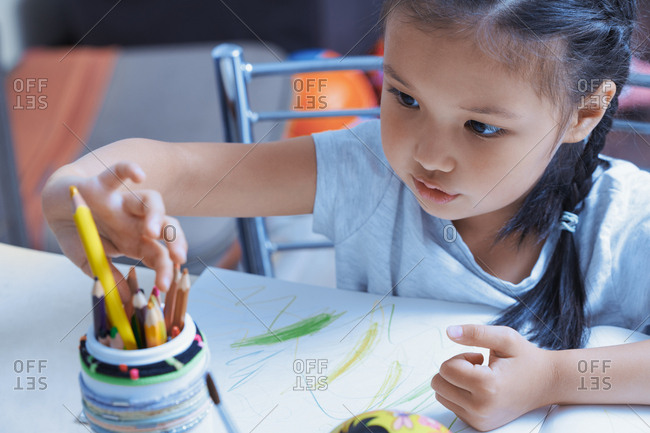 Girl picking up colored pencil from the jar