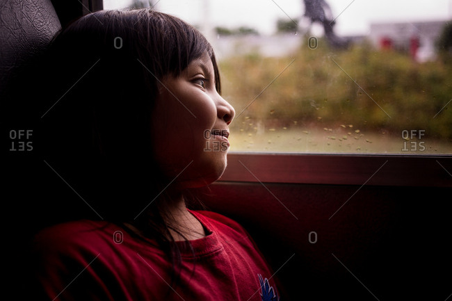 Portrait of girl looking out window of car