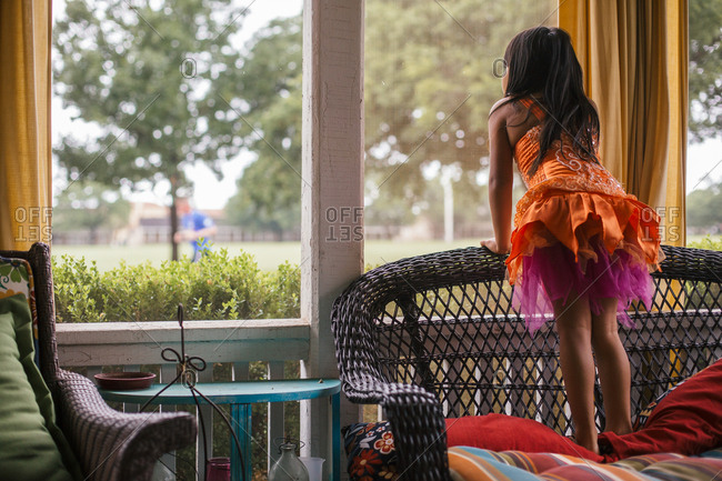 Girl playing dress up standing on chair and looking out window