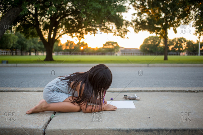 Girl on the sidewalk drawing a picture on a piece of paper