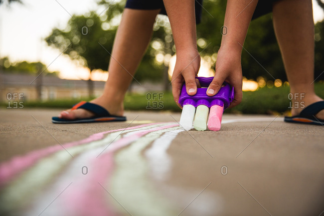 Child drawing on sidewalk with three pieces of chalk