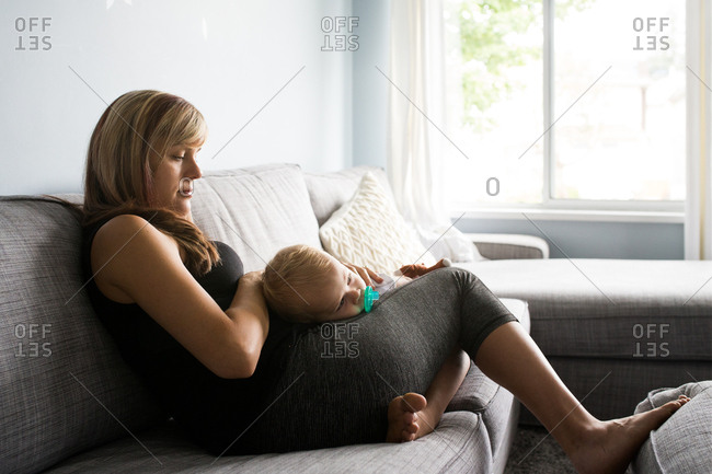 Mother and baby cuddling together on couch