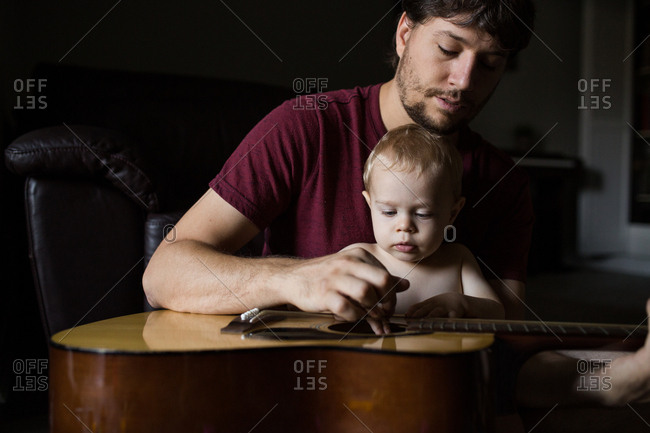 Father and baby son playing guitar together