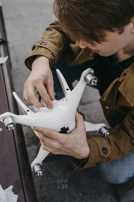 Handsome guy cleans and repairs drone before flight