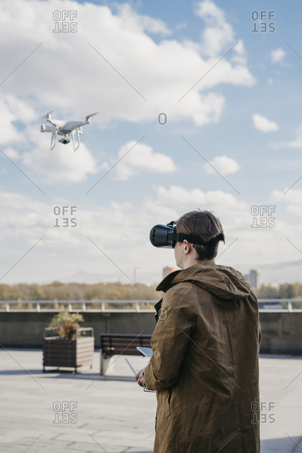 Young man using virtual reality to fly a drone