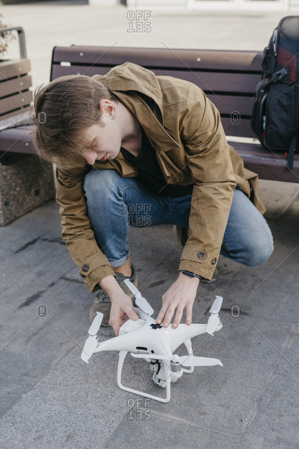 Close up of young man checkign the battery on a drone