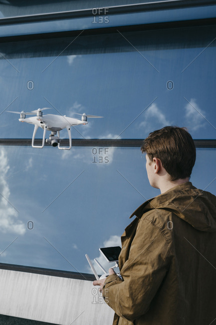 Young man holding a drone with a large glass building in the background