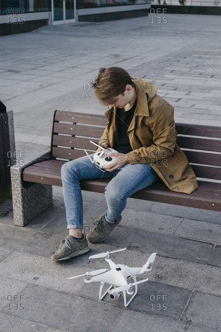 Young man sitting on a bench while flying his drone
