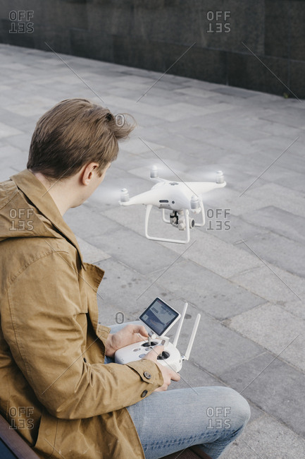 Young man sitting on a bench while looking at the remote that is flying his drone