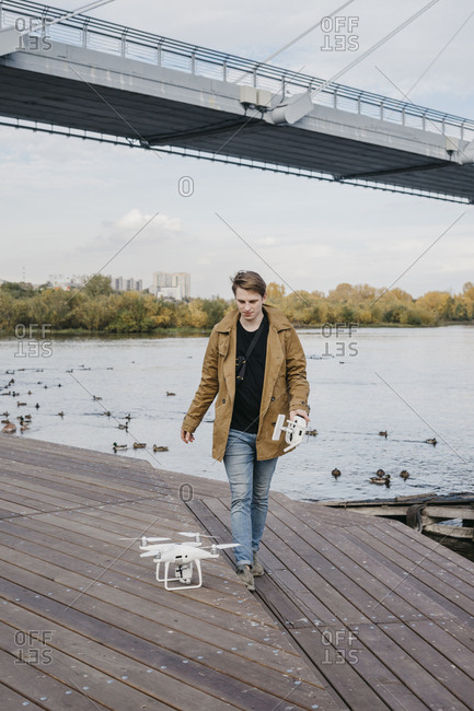 Young man walking by the water while flying his drone