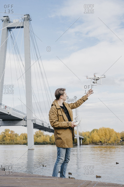 Young man flying his drone along a riverfront with a large bridge in the background