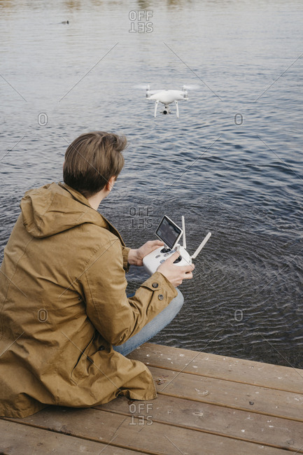 Young man flying his drone along a riverfront with ducks swimming by