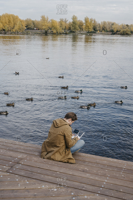 Young man flying his drone along a riverfront with ducks swimming behind him