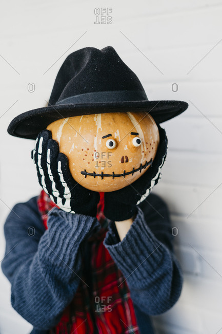 girl covers her face with a pumpkin decorated for Halloween