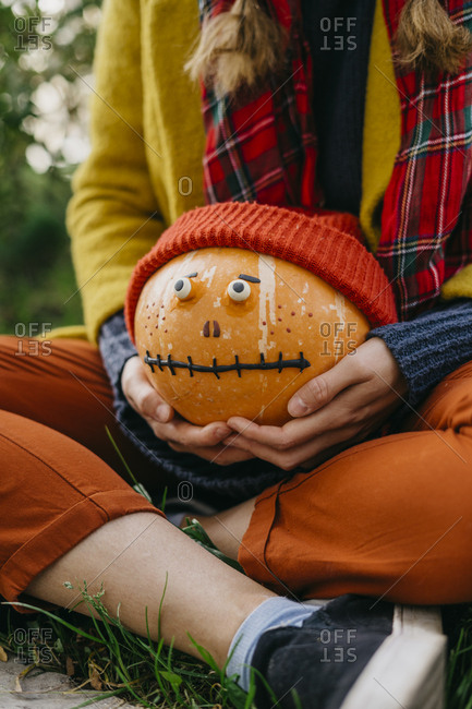 Girl holding a pumpkin with a face and wearing a Halloween outfit