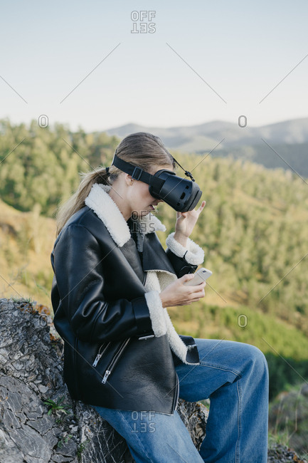 Portrait of a beautiful young woman wearing virtual reality glasses typing on a smartphone
