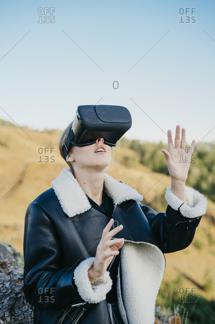 Portrait of a beautiful young woman in virtual reality glasses looks upward while raising her arms