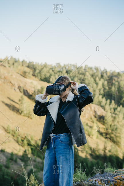 Portrait of a beautiful young woman wearing virtual reality glasses while sitting outside in a beautiful forest
