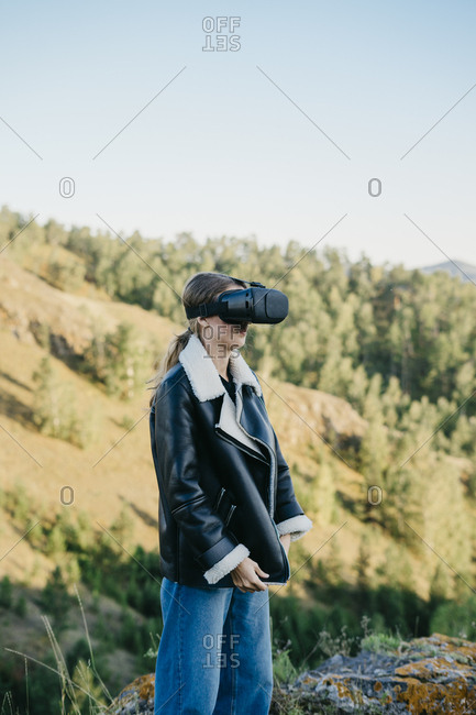 Portrait of a beautiful young woman wearing virtual reality glasses while buttoning her jacket