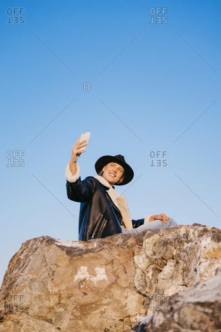 Portrait of a beautiful young woman in a black jacket and hat sitting on a rock while taking a selfie with her smart phone