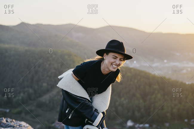 Portrait of a beautiful young woman in a black jacket and hat laughing while sitting on a rock