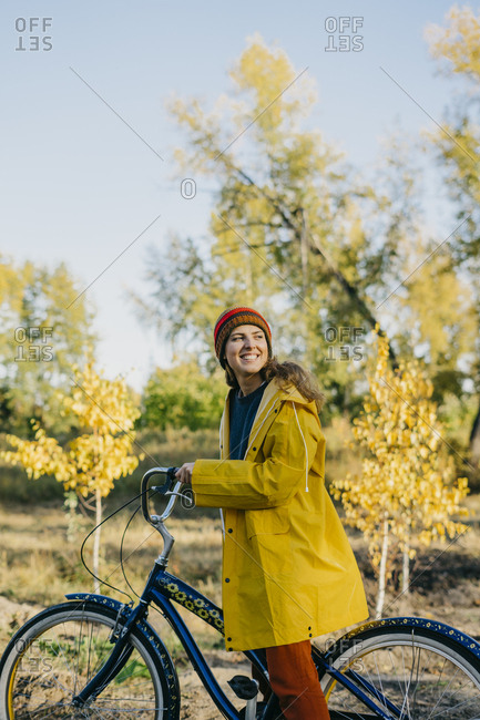 Beautiful young woman in a yellow raincoat on a retro bike in the autumn forest