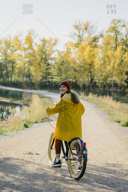 Beautiful young woman in a yellow raincoat riding a retro bike on a path in the park