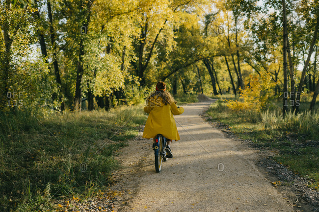 Young woman in a yellow raincoat while riding a bike through the forest