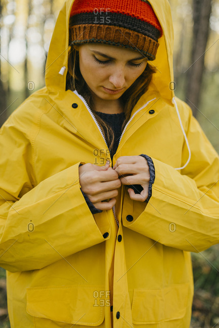 Beautiful young woman in a yellow coat standing looking out at the fall forest