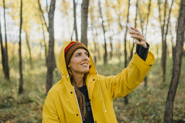 Portrait of a beautiful young woman in a yellow raincoat and knitted hat taking a selfie