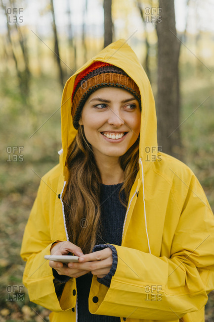 Portrait of a beautiful young woman in a yellow raincoat and knitted hat typing a message on her smart phone