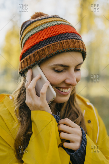 Portrait of a beautiful young woman in a yellow raincoat and knitted hat talking on her cell phone