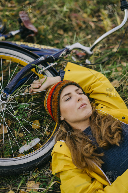 Portrait of a beautiful young woman in a yellow raincoat and knitted hat lying with her retro bicycle