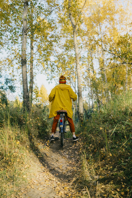 Portrait of a beautiful young woman in a yellow raincoat and knitted hat riding a retro bike in the autumn forest