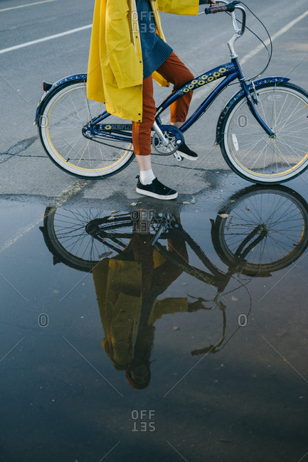 Portrait of a beautiful young woman in a yellow raincoat and knitted hat standing near a large puddle while on her retro bike
