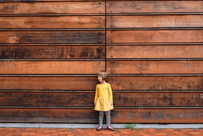 Toddler in yellow dress standing in front of a wooden wall