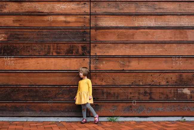 Toddler wearing yellow dress standing in front of a wooden wall