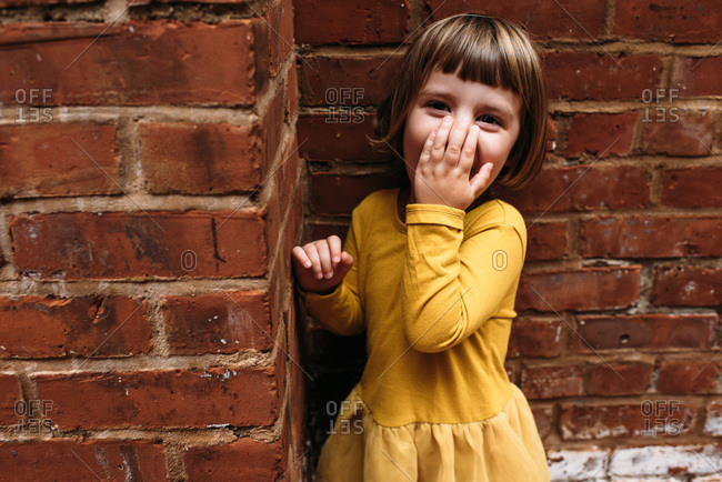 Little girl covering smile while standing by brick wall
