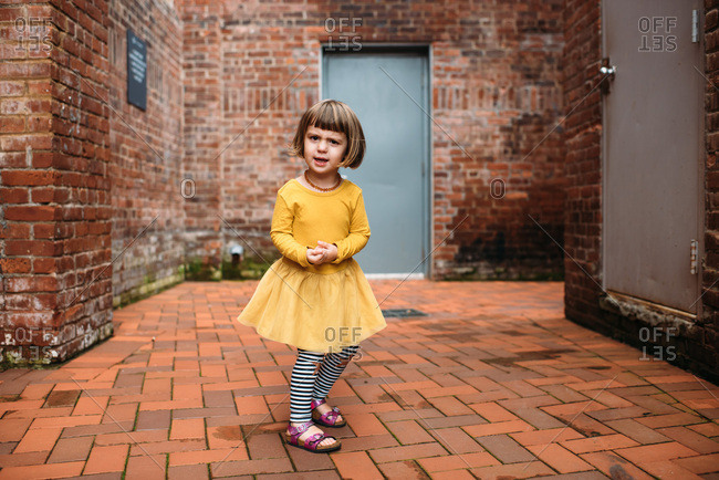 Little girl in yellow dress playing in a brick courtyard