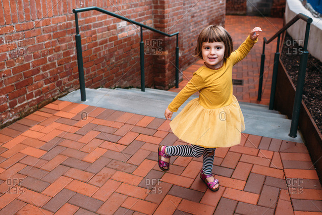 Girl in yellow dress playing in a brick courtyard