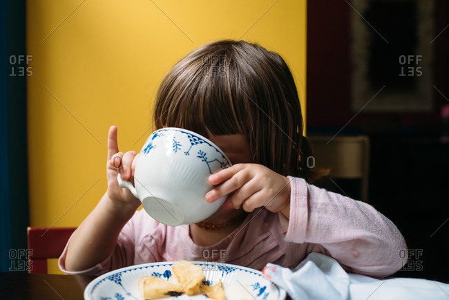 Little girl drinking from a tea cup with her pinky out