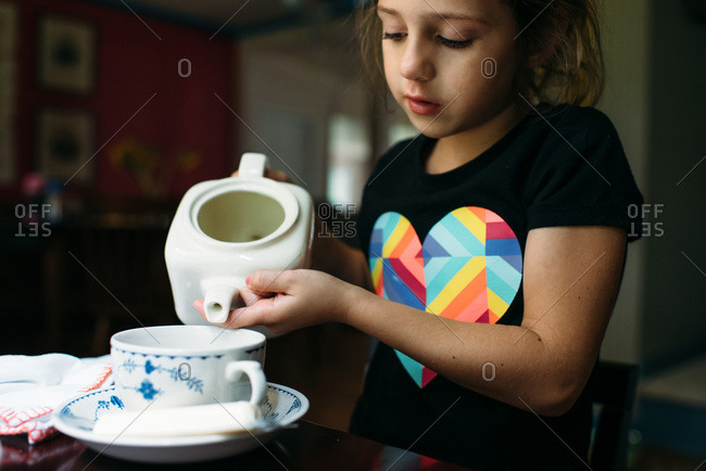Little girl pouring from a tea pot at a tea party