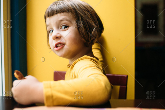 Little girl in yellow dress eating toast and being silly
