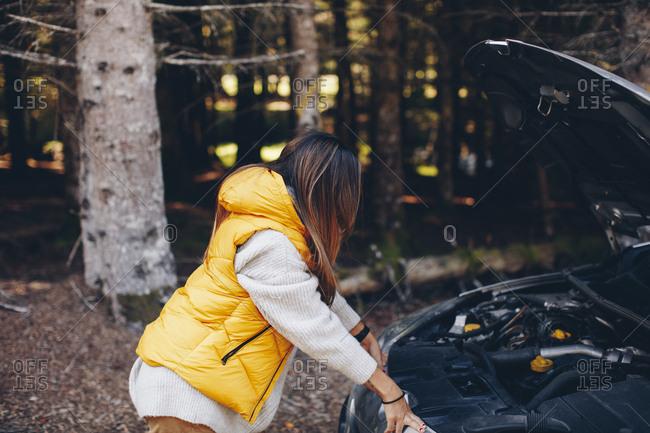 Woman looking under hood of her broke down car