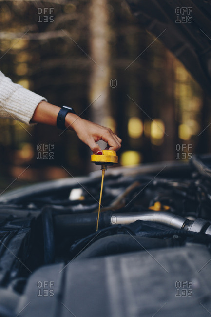 Woman holding dipstick while checking fluid levels of her broke down car