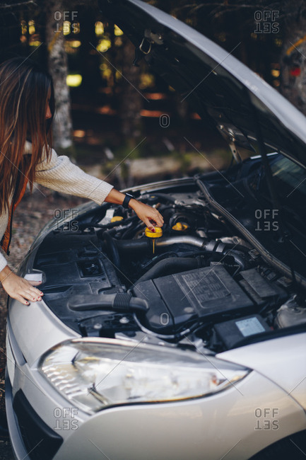 Woman checking fluid levels of her broke down car