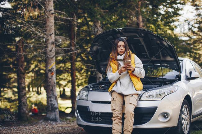 Woman calling roadside assistance after her car breaks down