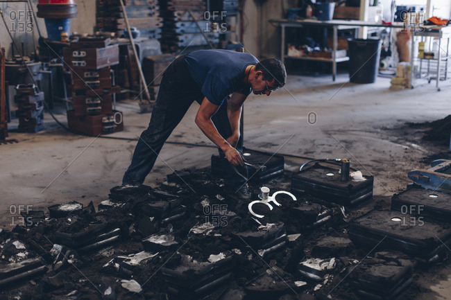 Worker in foundry removing metal objects from molds