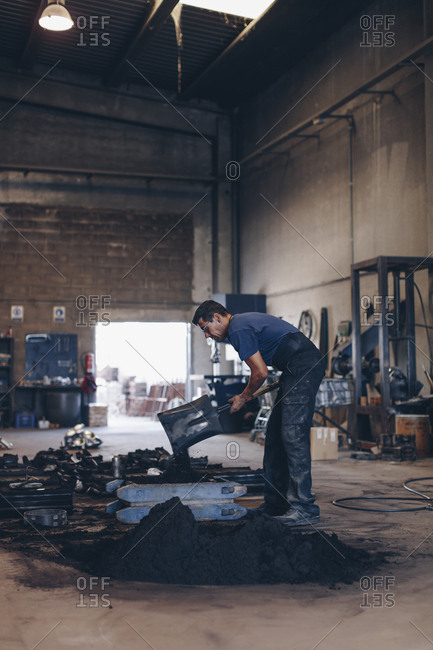 Foundry worker removing molds with a shovel